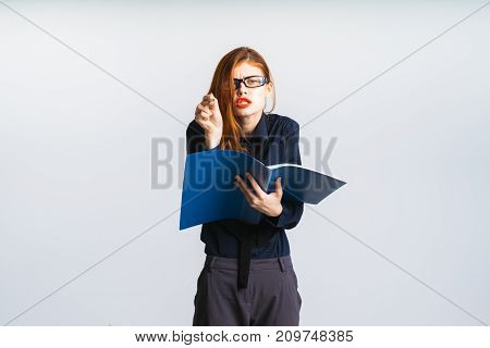 a tired girl in glasses holds an open blue folder in her hands and wants to write something down there