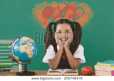 Illustration of light bulbs on yellow spray paint against schoolgirl reading a book against green background
