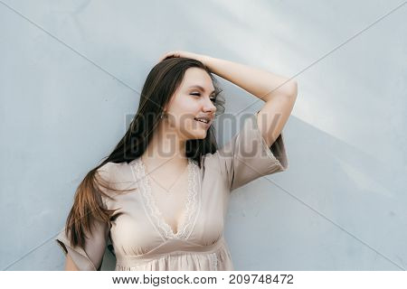 the lovely girl holds her long hair from the wind and looks away