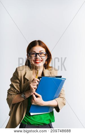 laughing red-haired girl with glasses is holding a bunch of folders and a pencil in her hands and looking into the camera