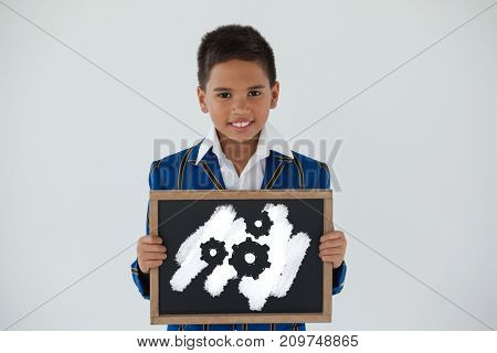 Digital composite image of gears on pink spray paint against schoolboy holding blank writing slate against white background