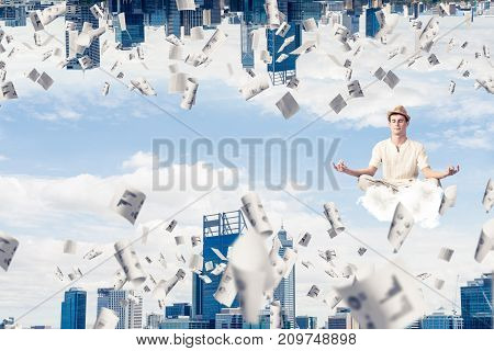 Young man keeping eyes closed and looking concentrated while meditating on cloud among flying papers and between two worlds.