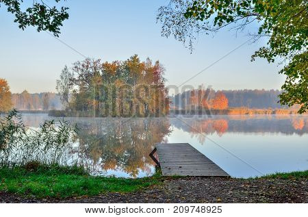 Beautiful autumn landscape. Wooden pier and island with trees on the lake.