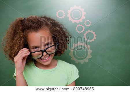 Cute pupil tilting glasses against digital composite image of gears