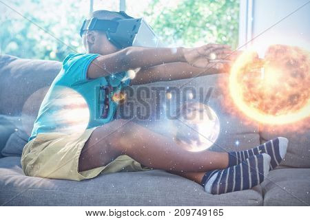 Composite image of solar system with sun against side view of boy wearing virtual reality headset with arms raised at home