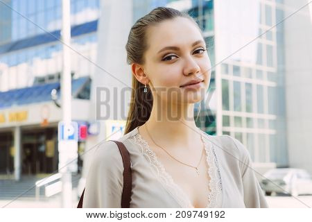 lovely pretty girl on a walk in the city stands on the background of a beautiful multi-storey building