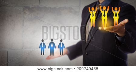 Unrecognizable business manager is lifting a winning team of three male employees above a group of average performers. Human resources metaphor for team effort career success hiring and coaching.