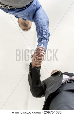 Businessmen shaking hands on a deal or agreement in welcome or in congratulations low angle view.