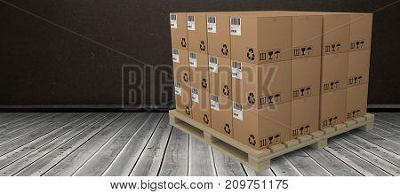 Cardboard boxes arranged on wooden pallet against dark room