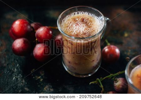 Grape lassi - made from fresh grapes on black table.