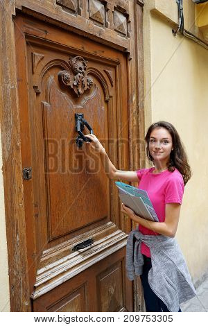 Young traveling girl standing near an old door. Travel in Spain.