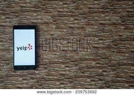 Los Angeles, USA, october 19, 2017: Yelp logo on smartphone screen on stone facing background