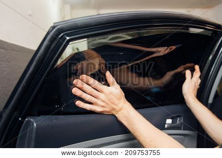 Master installs a tint film for the car glass with a hairdryer and spatula with glare of light. Concept tinting car poster