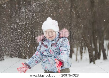 Laughing little girl is tossing up winter snow with her hands