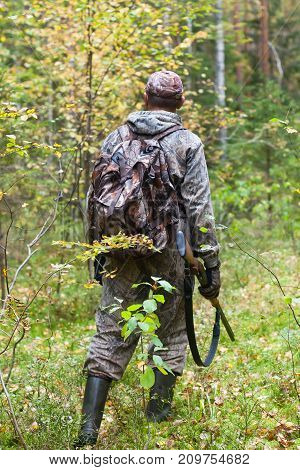hunter with hunting gun in the autumn forest
