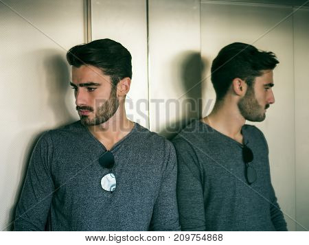 Handsome young man leaning against mirror inside an elevator or lift, looking down to a side