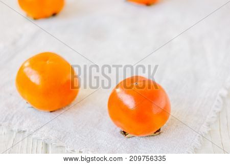 Group of ripe persimmons on white fabric material