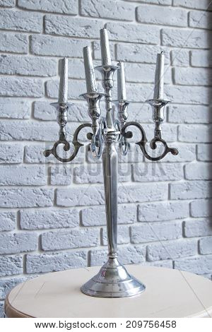 Silver Candelabra five candles, grey background, on the table.