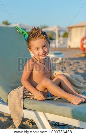 Portrait smiling little baby boy sitting near the sea ocean. Positive human emotions feelings joy. Funny cute child making vacations and enjoying summer.