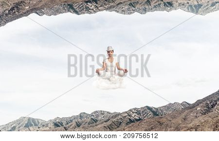 Young woman keeping eyes closed and looking concentrated while meditating on cloud in the air between two nature worlds.