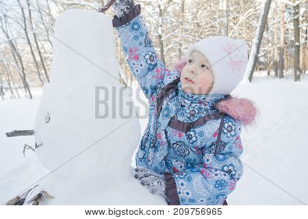 Little girl is decorating winter snowman outdoors