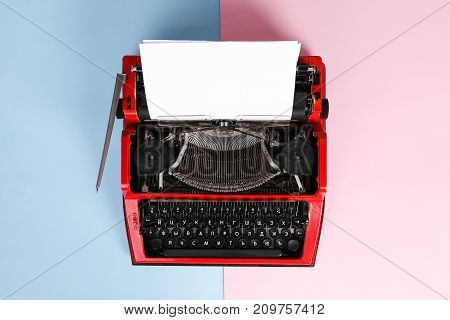 Vintage photo of red typewriter over a pastel background. Red typewriter. The writer's tool