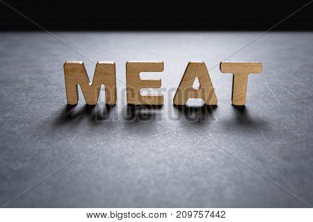 Word Meat Of Wooden Letters On A Dark Texture With A Black Background With Backlight. Lighting Effec