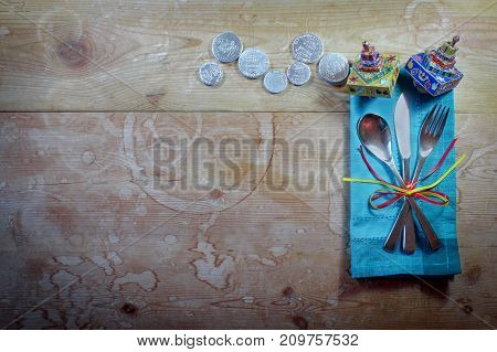Casual Hanukkah dinner place setting with colorful napkin, dreidels, and gelt on old wood table