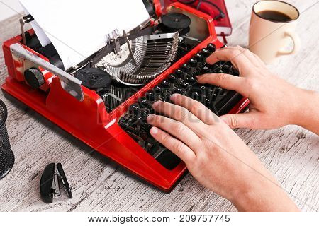 Vintage red typewriter on the table with hands