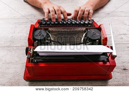 Vintage red typewriter on the table with hands and paper. Close-up photo