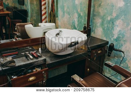 The workplace with a washbasin in barbershop. Interior of luxury beauty salon.