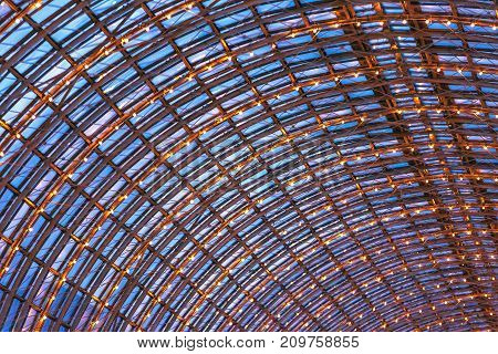 An abstract image of the roof of a large mall a steel frame with glass decorated with decorative lamps with a warm yellow color a night photograph with blue windows. Semicircular GUM roof, Moscow.
