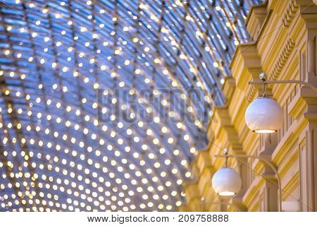 Designer glass white lamps hanging on the wall. Against the background of the roof of the shopping center. Copy space for text. Semicircular GUM roof, Moscow.