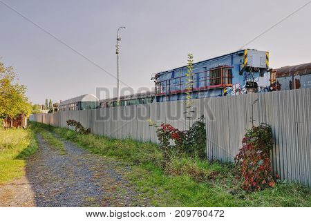 Lovosice, Czech Republic - September 29, 2017: Locomotive And Wagon Wrecks Behind The Fence Of The M