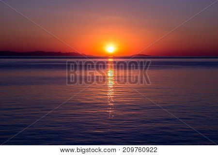 Sunset over sea horizon. Bright sun is reflected from water surface, evening sky.