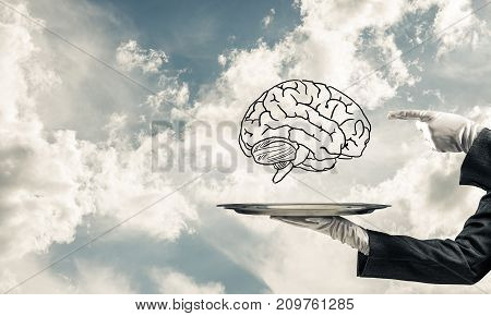 Cropped image of waitress's hand in white glove presenting sketched brains on metal tray and pointing on it with cloudy skyscape on background. 3D rendering.