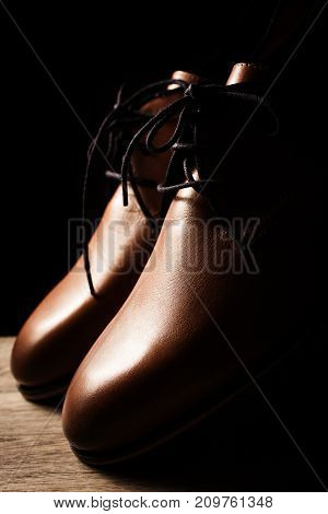 Closeup of male brown shoes over black background