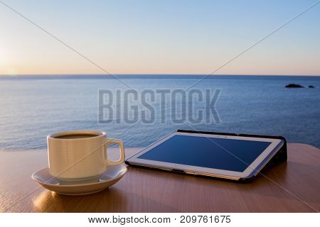White tablet ipad on table desk with coffee cup, with sea landscape.