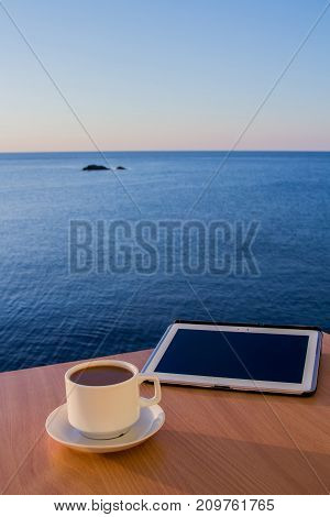 White tablet ipad on table desk with coffee cup, with smooth sea landscape, daytime.