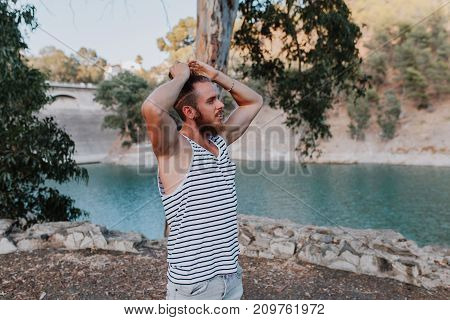 Bearded cool man making himself a long hair pony in nature.