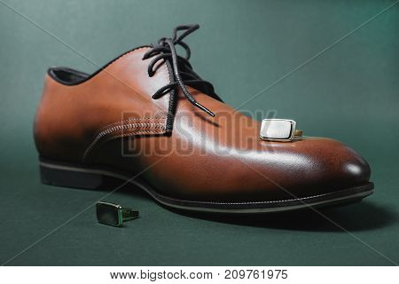 brown male shoes and cuff in grey background