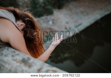 Woman looking out through a bridge, with a hand floating in the air.
