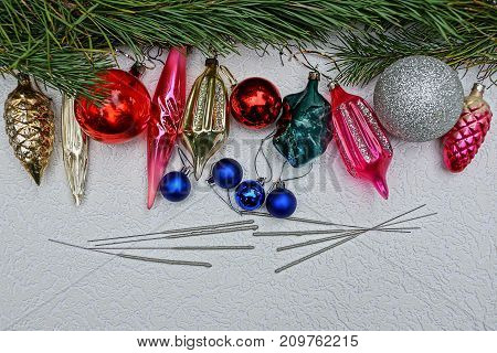 New Year's bright toys with Bengal lights and pine branches on a gray background