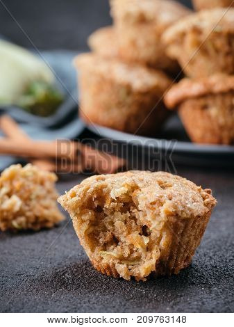 Close up view of muffin with zucchini, carrots, apple and cinnamon on black cement background. Sweet vegetables homemade muffins. Toddler-friendly recipe idea. Copy space. Shallow DOF