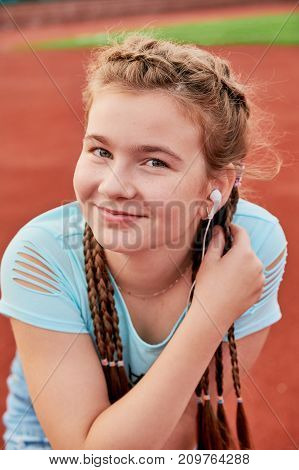 Sporty pretty teen girl loves sports.Closeup portrait of a teenage girl with a smile.outdoor stadium girl listening to music on headphones.