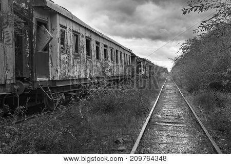 Hopeless post apocalyptic landscape. Cemetery of abandoned broken trains. Monochrome photo.