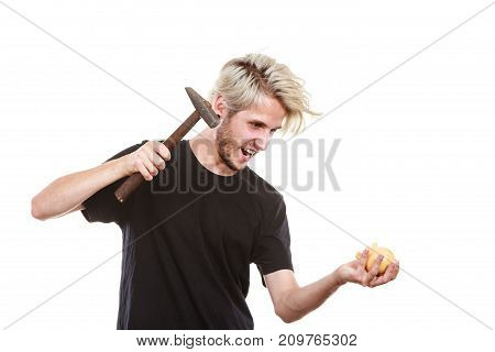 Money savings finances concept. Angry sreaming young blonde man wearing black t shirt trying to break piggy bank with hammer studio shot isolated
