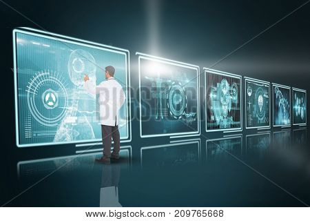 Handsome doctor pointing against composite 3D image of different application interface