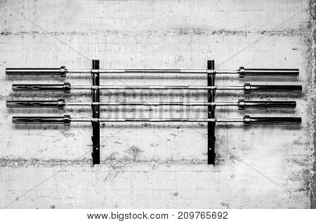 Four barbell weight bars on the stand screwed on the grunge wall prepared for bodybuilding weightlifting sport in the gym