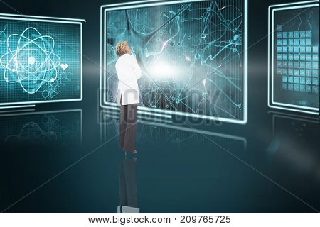 Blonde doctor standing against composite 3D image of different interface